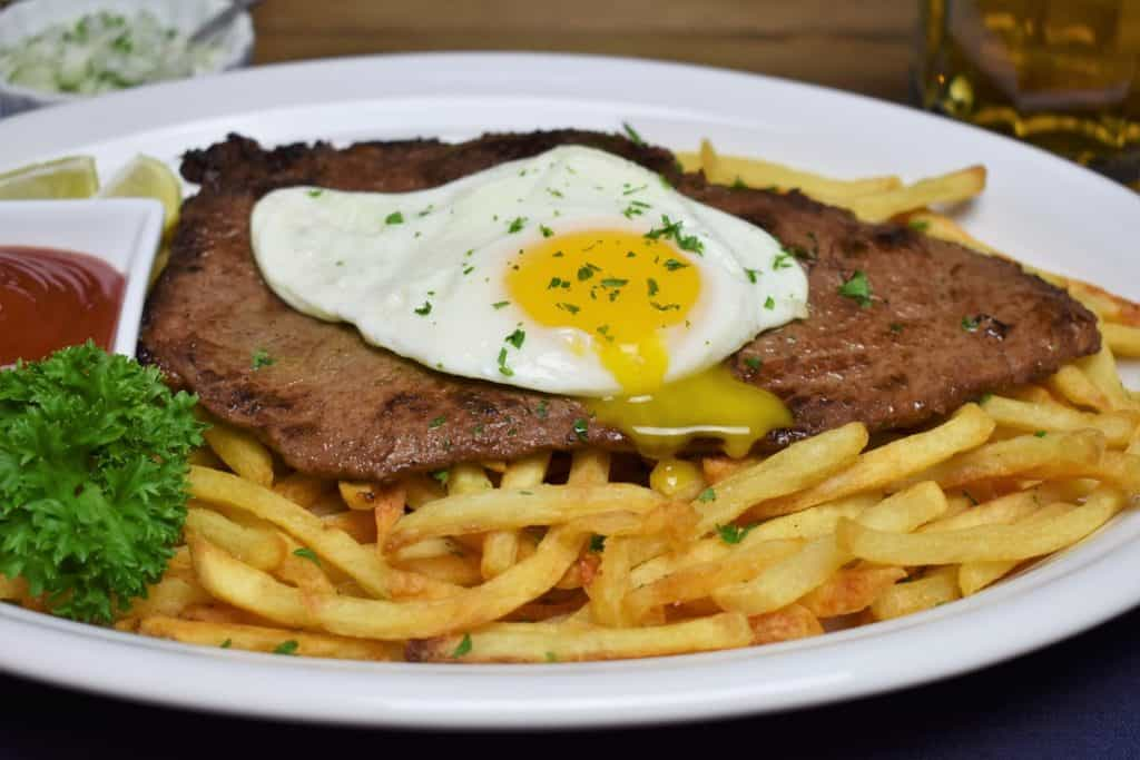 Bistec a Caballo a thin, pan fried steak served on a bed of fries and topped with a fried egg with the yolk pierced and running into the fries