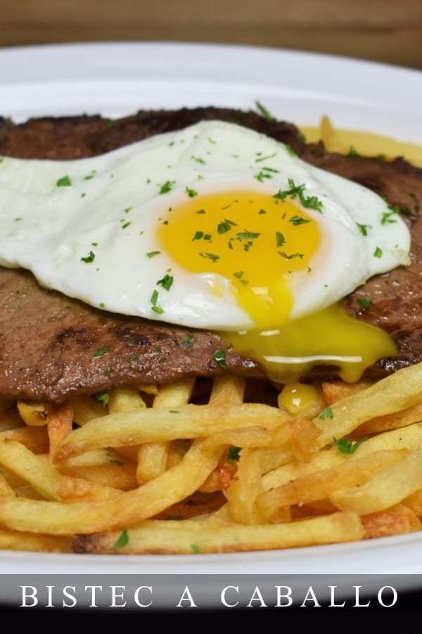 Bistec a Caballo is the Cuban equivalent to steak and eggs. This dish is simple to make, it's a thin steak that's quickly pan-fried, served on a generous bed of French fries and topped with a fried egg. #bistecacaballo #steakandeggs #cubanfood #cubanrecipes #cubanbistecacaballo