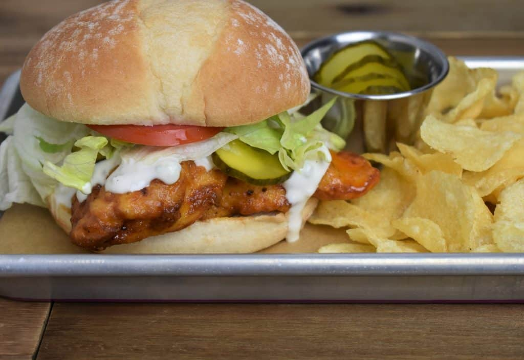 Buffalo Chicken Sandwich served with lettuce, tomato, pickles, and blue cheese dressing on a bun with a side of chips