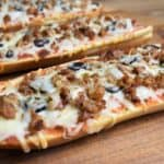 Hot Sausage French Bread Pizza served on a wood cutting board