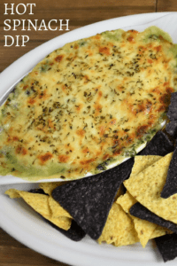 Hot Spinach Dip served with corn tortilla chips in a large white platter.