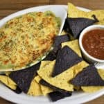 Hot Spinach Dip topped with melted, mozzarella cheese and served on a large platter with corn tortilla chips and salsa on the side