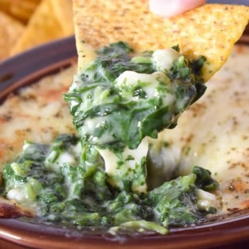 Creamy spinach and cheese being scooped out of a brown crock with a corn tortilla chip.