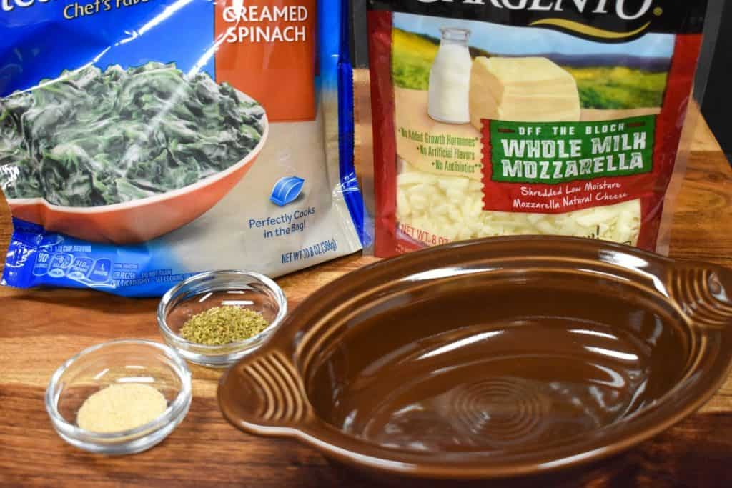 The ingredients for the hot spinach dip in their packages displayed on a wood cutting board.