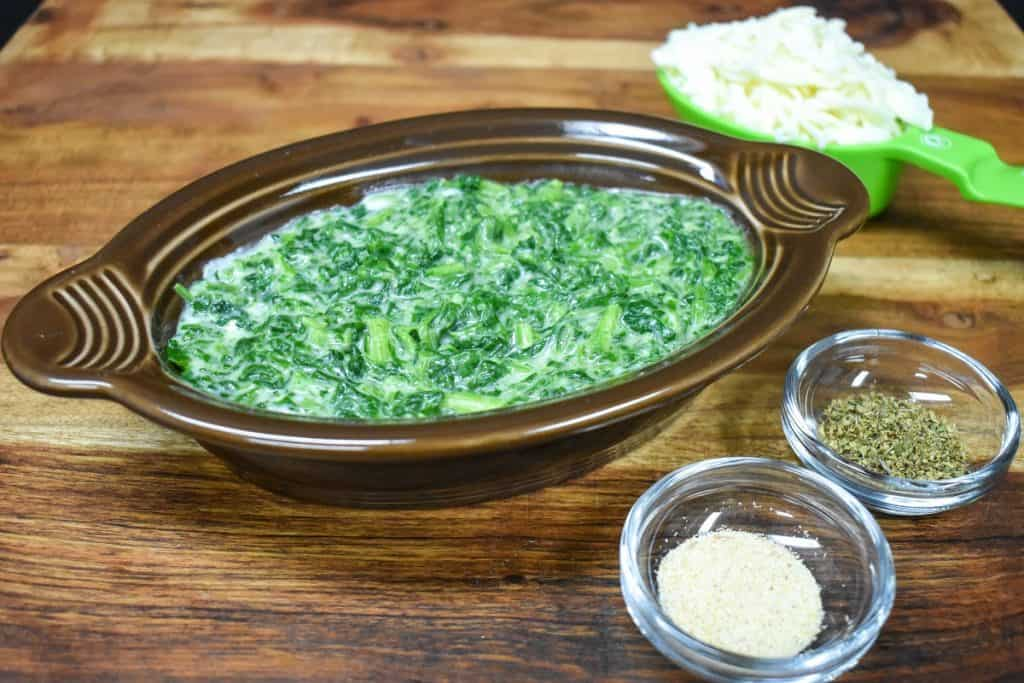 Creamed spinach in a brown bowl displayed on a wood cutting board.