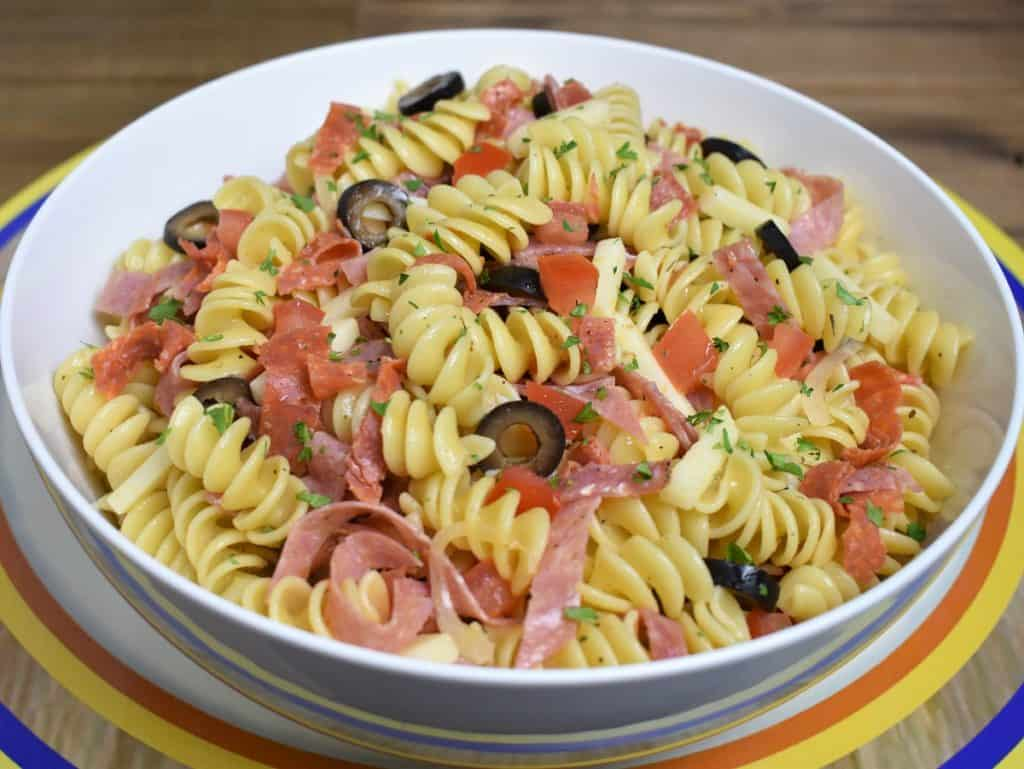 Italian Pasta Salad, rotini pasta with sliced salami, provolone cheese, sliced olives served in a white bowl