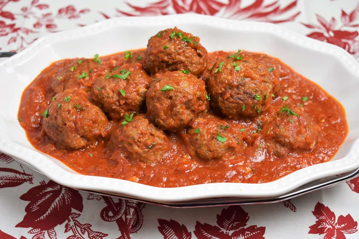 Meatballs Cuban Style served on a white platter in a red sauce and garnished with chopped parsley