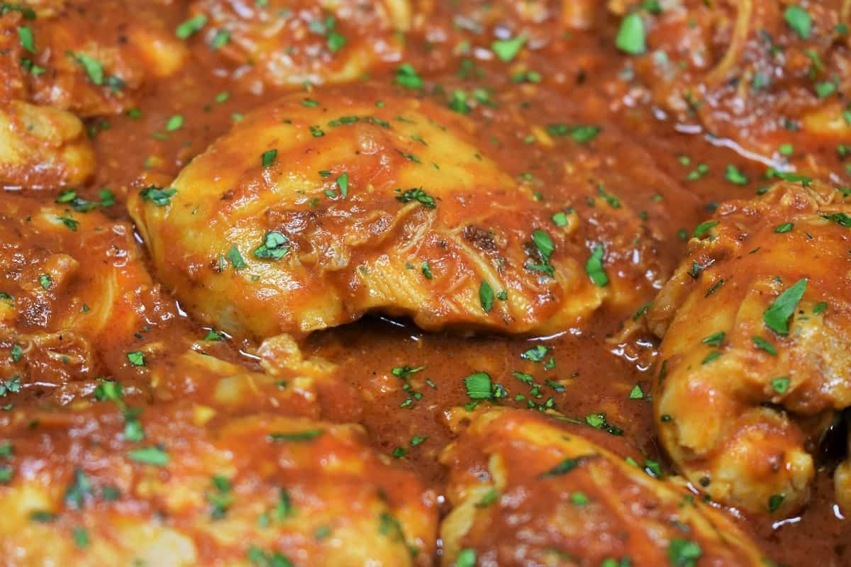 A close up picture of chicken in red sauce, garnished with parsley
