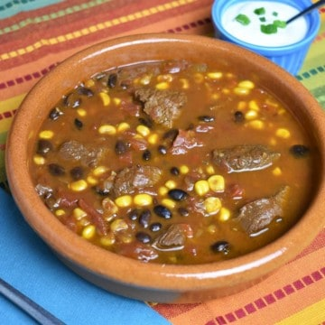 Southwestern Steak Soup with chunks of beef, black beans, tomatoes,and corn in a beef broth, served in a red clay bowl with sour cream on the side.