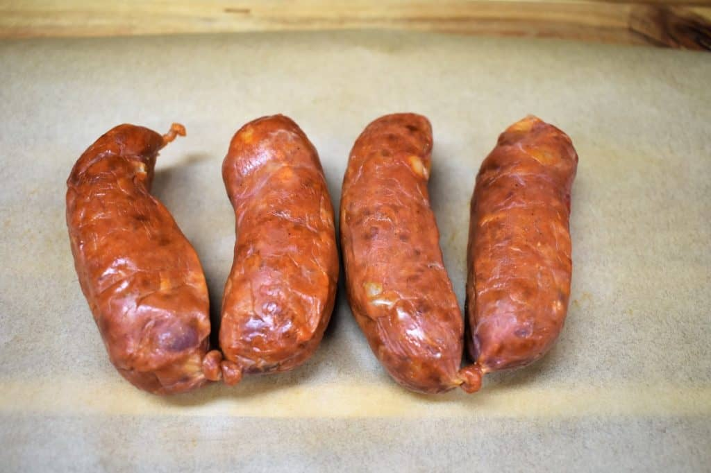 Four Spanish Chorizo Links on parchment paper displayed on a wood cutting board