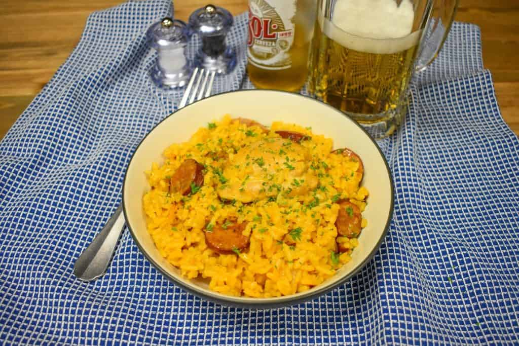 Yellow Spanish rice with chicken and sausage served in a white bowl and displayed on a blue checkered cloth with a beer in the background.