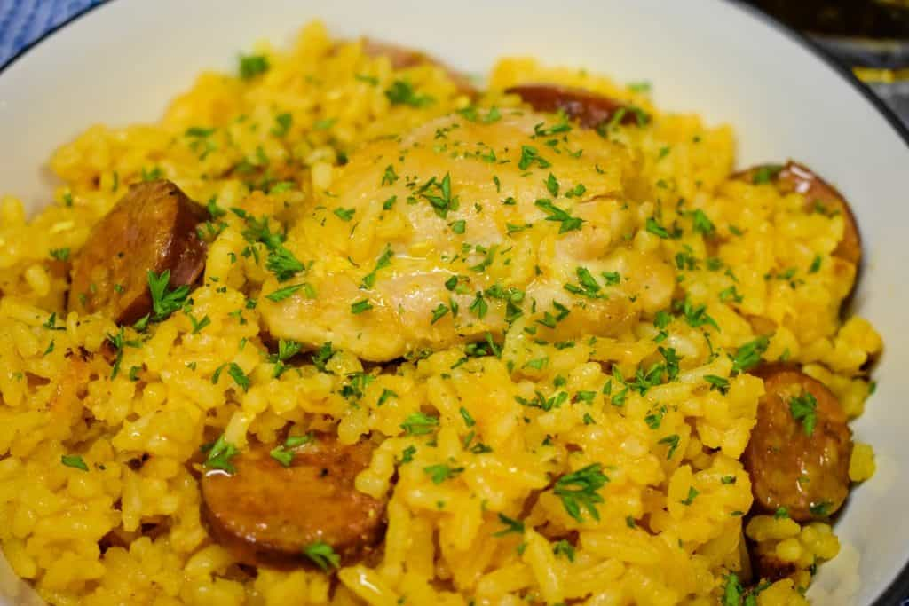 Yellow Spanish Rice with chicken and sausage served in a white bowl.