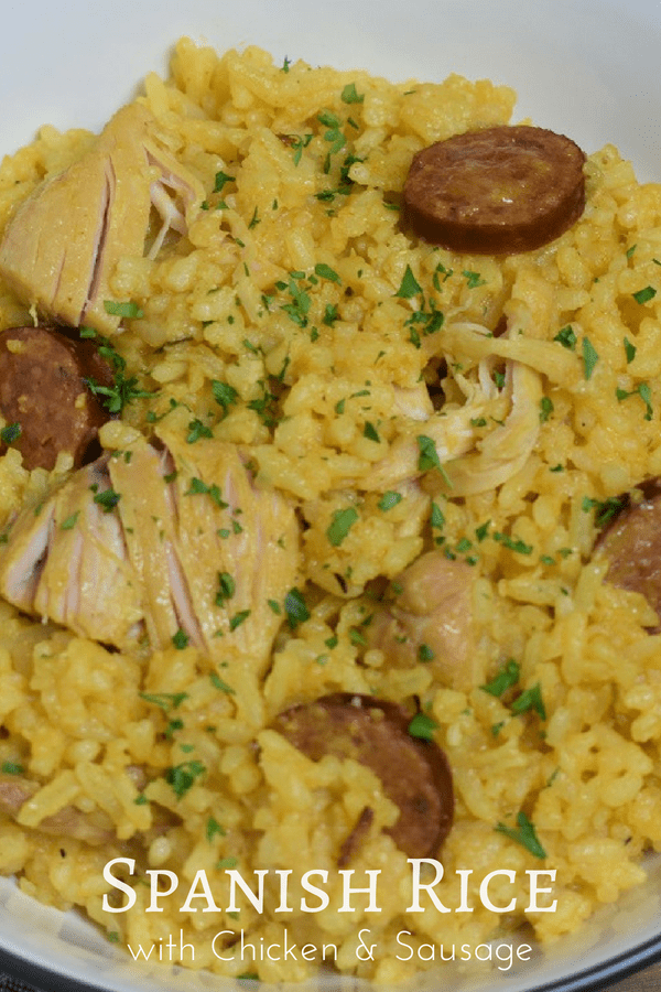 This Spanish rice with chicken and sausage is a stick-to-your-ribs kind of dinner. It's not fancy but it sure is good. Chicken thighs and andouille sausage are cooked with onions, lots of garlic and a combination of spices. The rice is cooked in the same pot, we even add a beer, arroz con pollo-style, to help steam the rice. #spanishrice #rice #ricechickensausage #yellowrice #chickenandrice #cook2eatwell