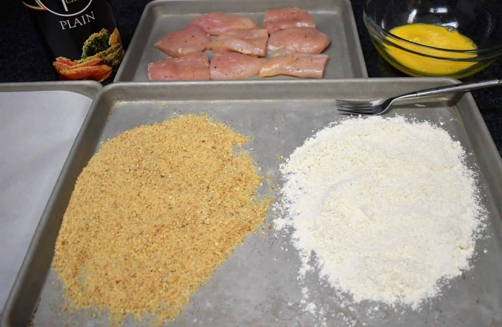 Breading Station, with flour and breadcrumbs on a pan, a beaten egg in a bowl and chicken breast cutlets in the background