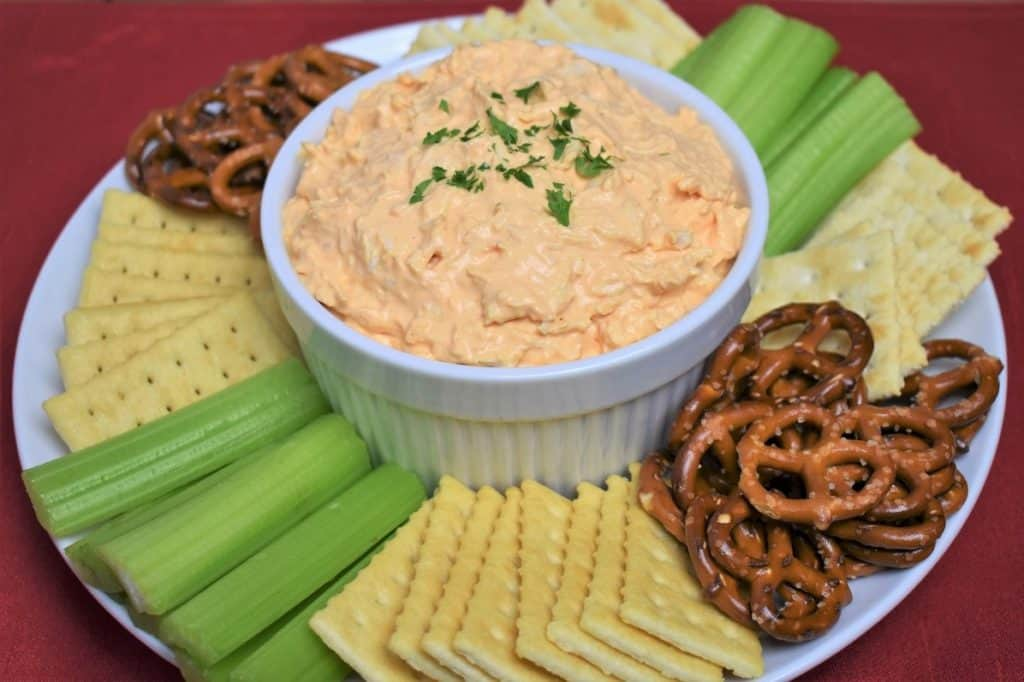 Cold Buffalo Chicken Dip served in a white bowl with assorted crackers, celery sticks and pretzels arranged on the plate.