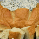Creamy Spinach Dip served in a bread bowl with bread cubes arranged around it.