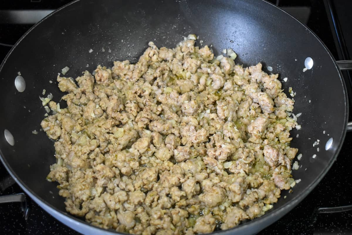 Browned Italian sausage crumbles in a black skillet.