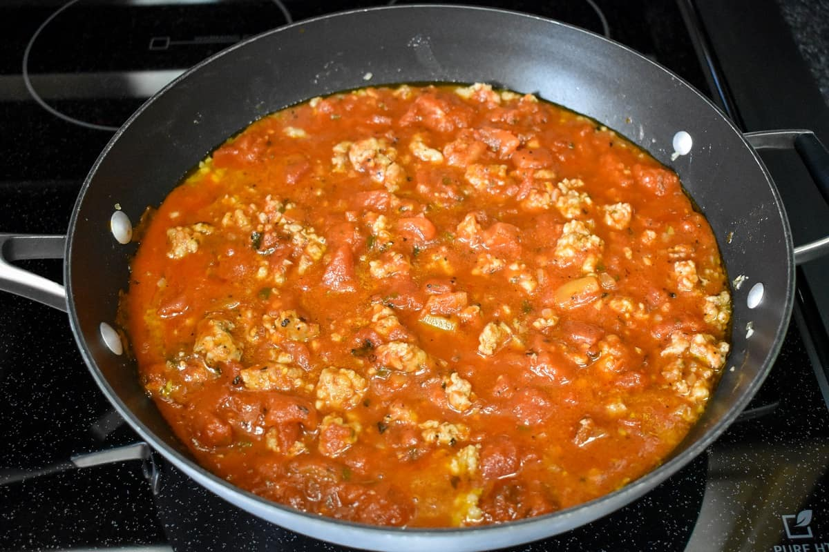 The Italian sausage sauce in a large, black skillet.
