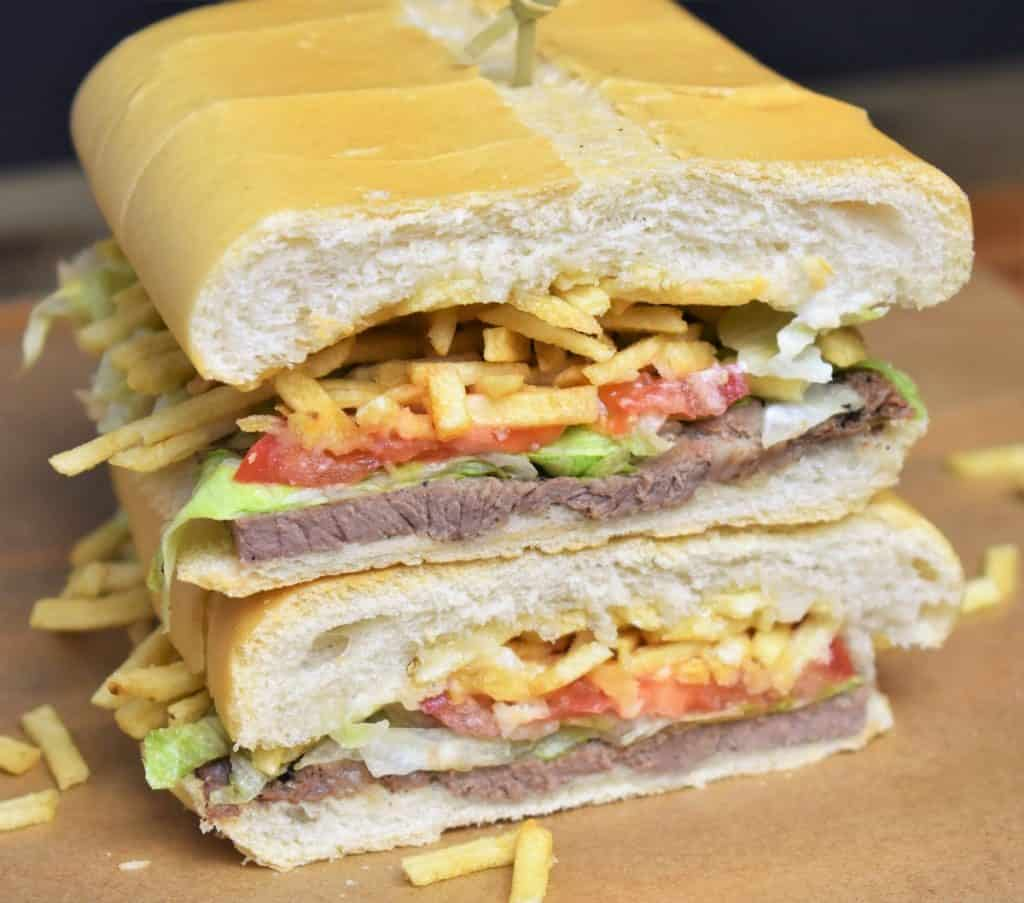 Pan con Bistec sandwich cut in half and stacked.