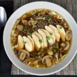 Soba Noodle Chicken Soup with mushrooms, green onions and sesame seeds served in a large, shallow light colored bowl