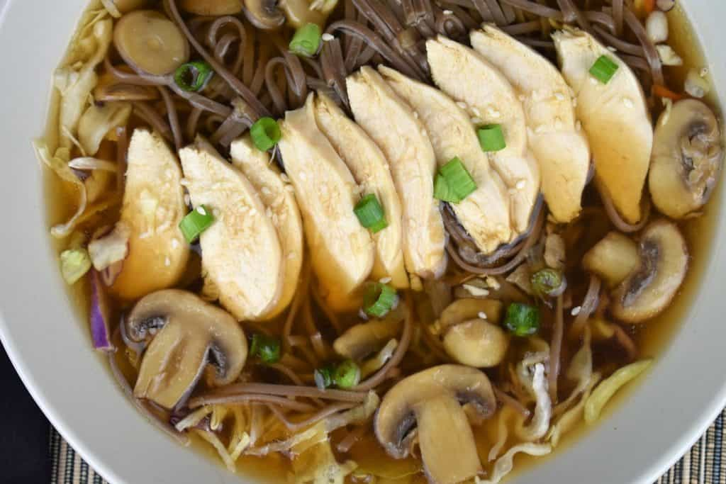 A close up of soba noodle chicken soup with mushrooms, green onions and sesame seeds.