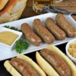 Beer brats, sausages arranged on a white platter with two of the brats served on buns with a small ramekin of mustard and a ramekin of cooked, sliced onions on the side
