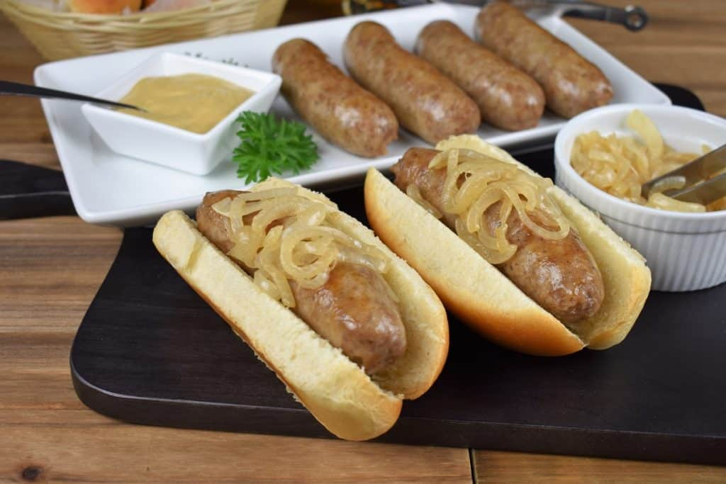 Beer brats, sausages arranged on a white platter with two of the brats served on buns and topped with cooked onions