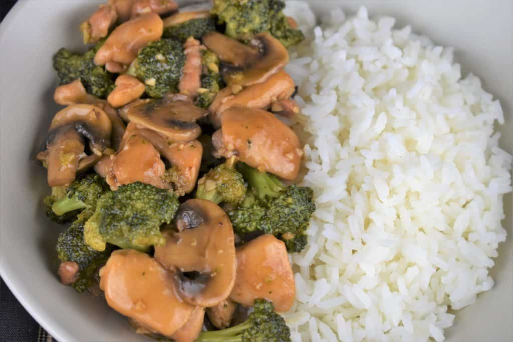 A close up of Chicken Broccoli Mushrooms Stir Fry with white rice on the side
