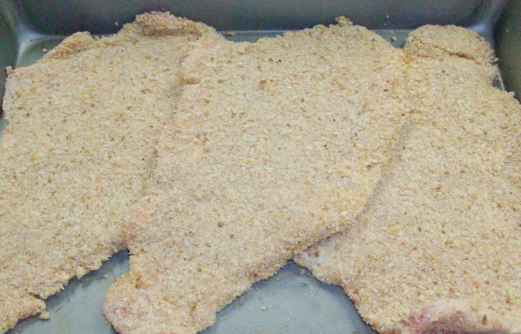 Uncooked breaded pork steaks displayed on a metal baking sheet.