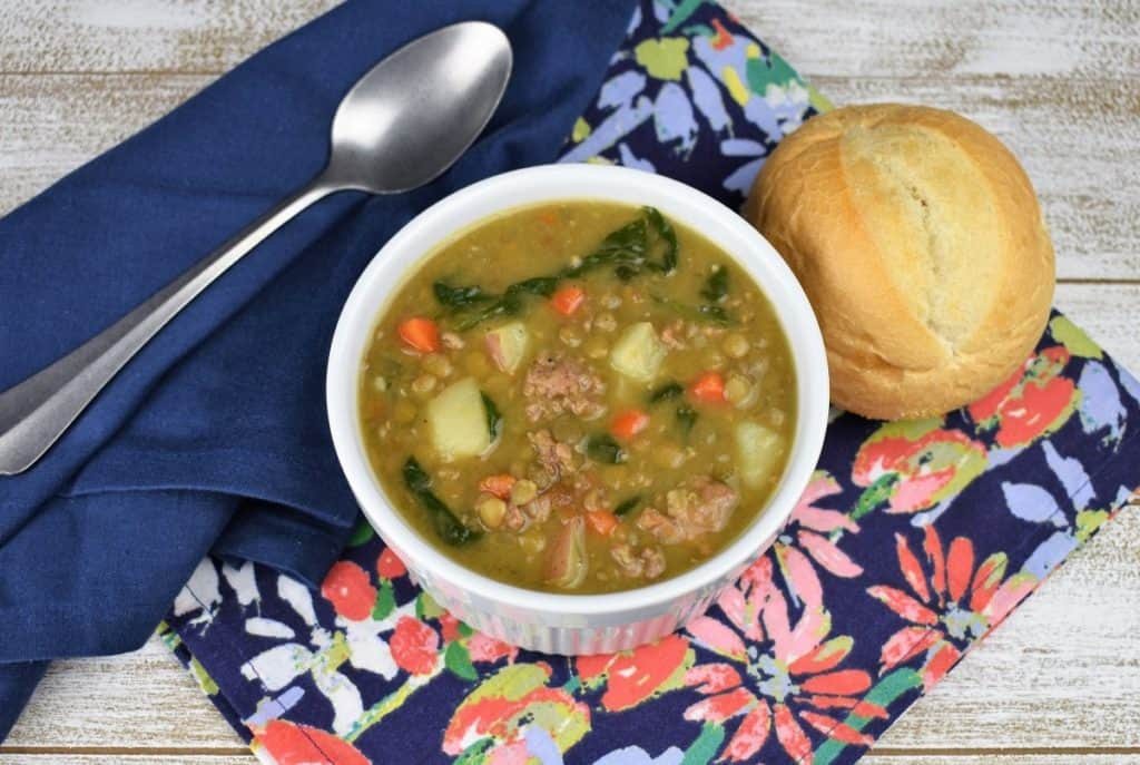 Italian Sausage Lentil Soup served in a white bowl with a roll on the side