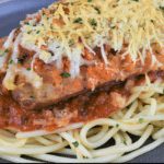 Italian Sausage Parmigiana on a bed of spaghetti