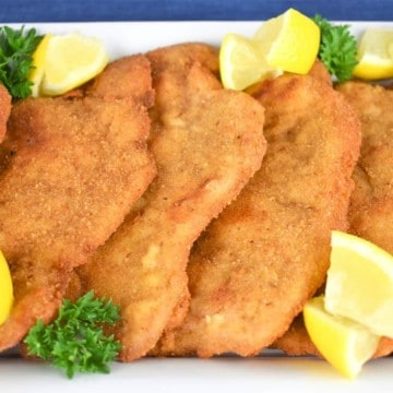 Pork Schnitzel arranged on a white platter and garnished with fresh parsley and lemon wedges.