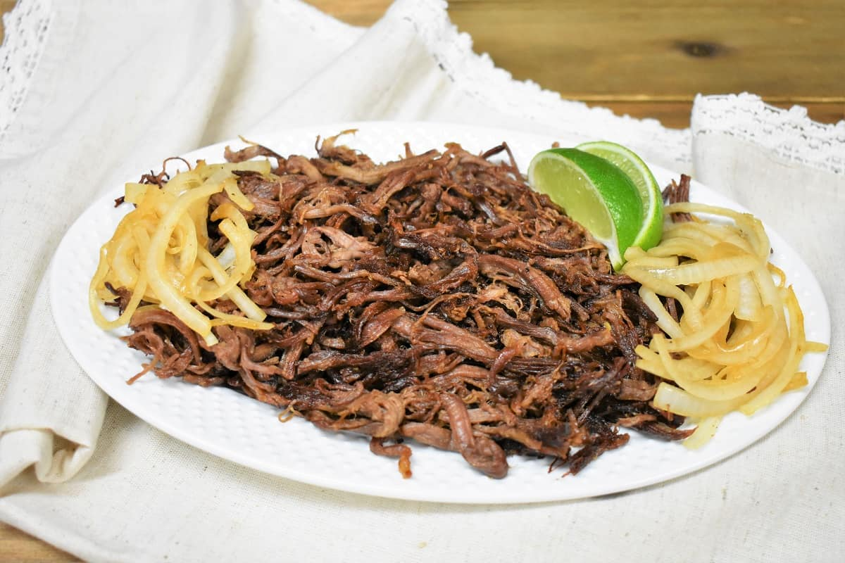 Vaca Frita served on a white platter and garnished with cooked onions and lime wedges on the side.
