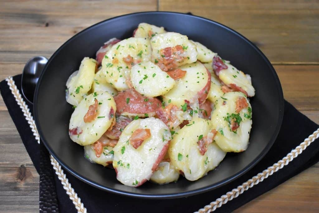 Warm potato salad served in a large black bowl.
