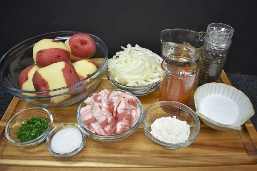The ingredients for warm potato salad arranged on a wood cutting board.