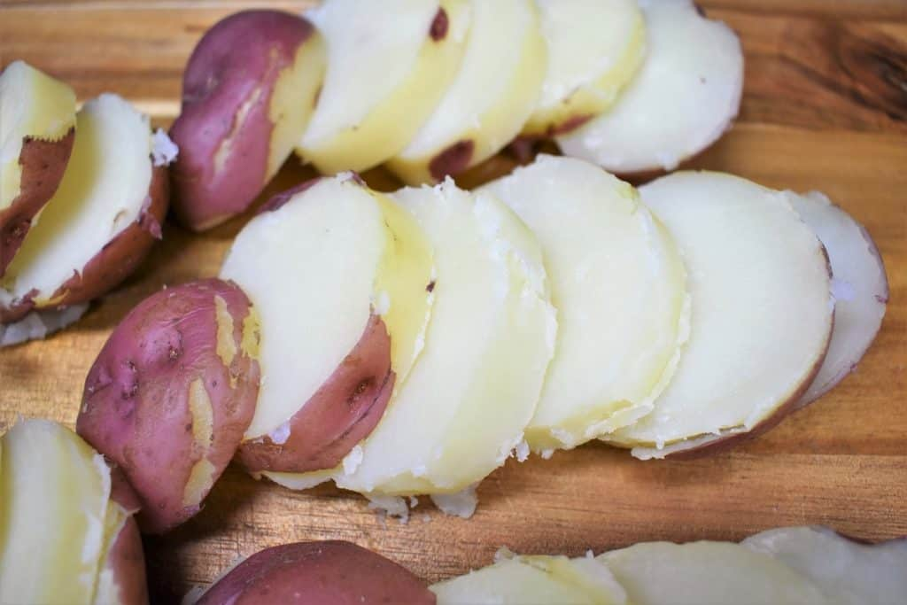 Red potatoes cut into thick slices arranged on a wood cutting board.