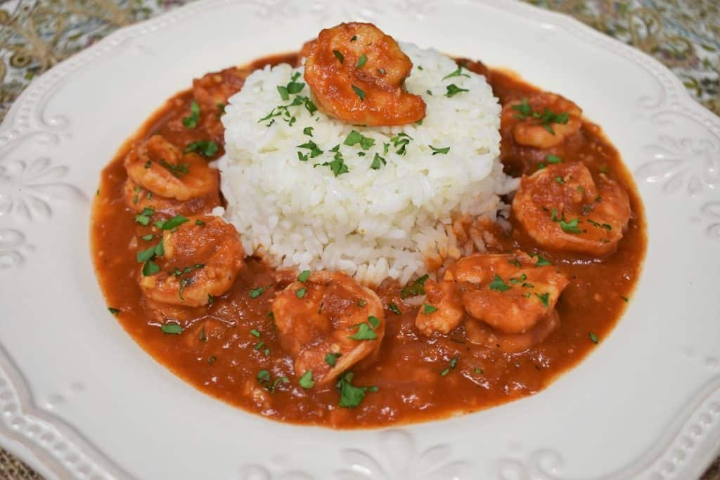 Camarones Enchilados, shrimp in a red sauce arranged around white rice and garnished with chopped parsley