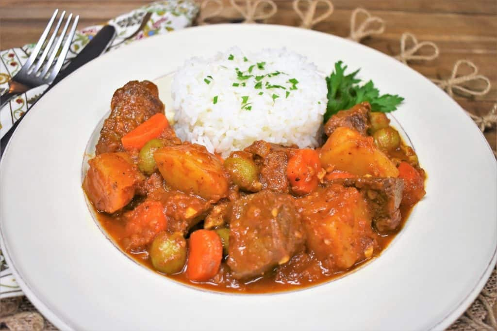 A close up picture of beef chunks and potatoes in a red sauce with olives, carrots and side of white rice, served in a white plate.