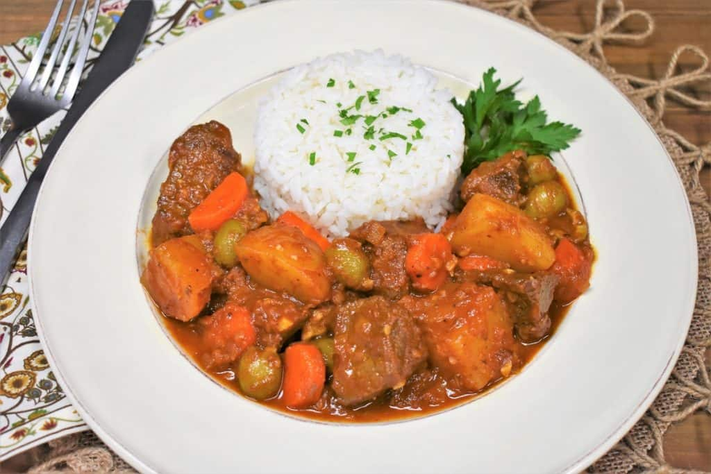 Beef chunks and potatoes in a red sauce with olives, carrots and side of white rice, served in a white plate.
