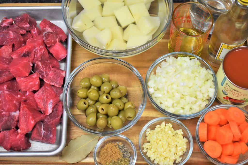 The ingredients for carne con papas displayed on a wood cutting board.