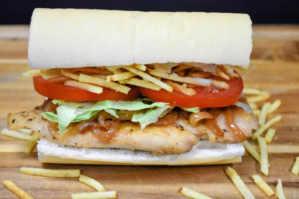 A Cuban chicken sandwich displayed on a wood cutting board. A thin chicken breast on Cuban bread topped with shredded lettuce, sliced tomatoes and potato sticks.