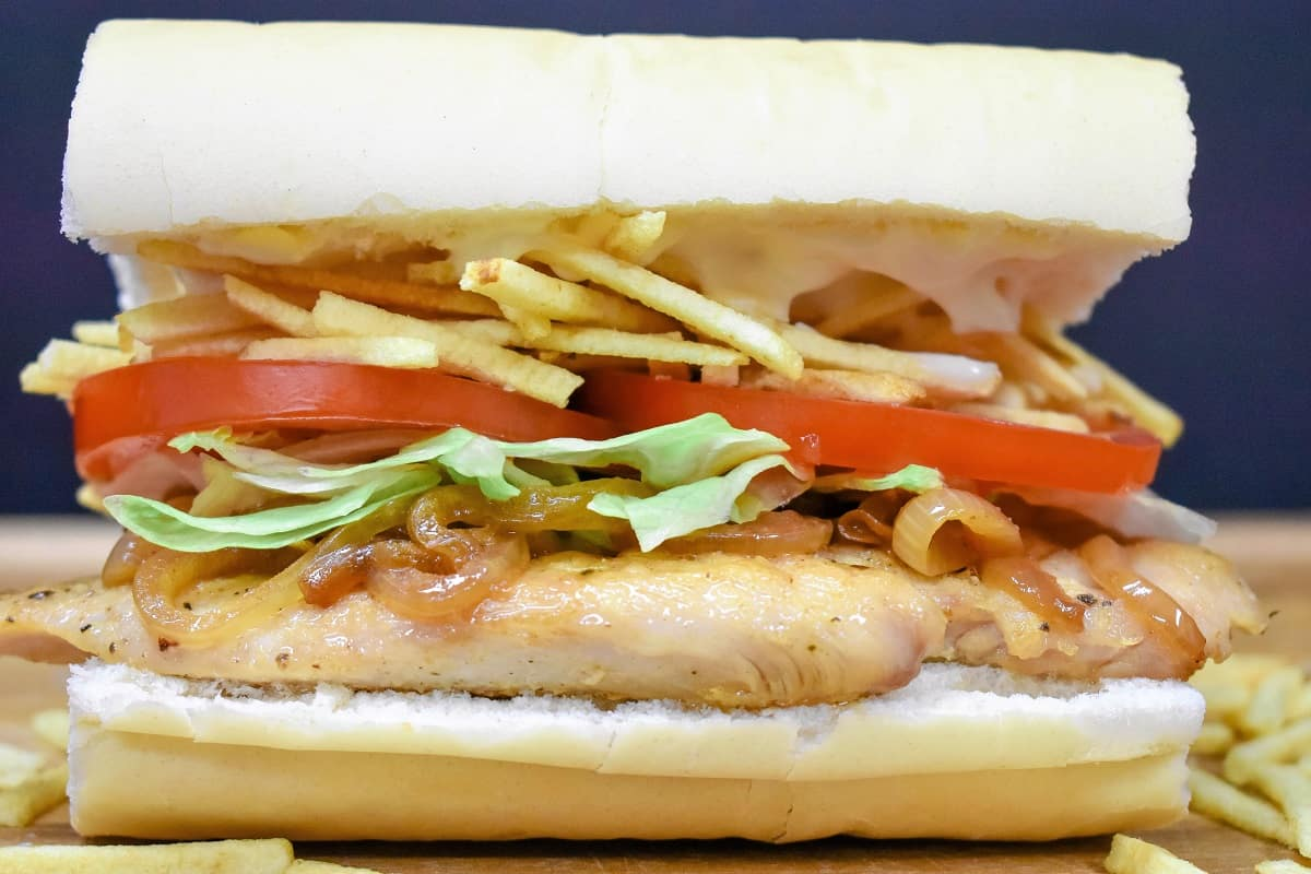 A thin chicken breast on Cuban bread topped with shredded lettuce, sliced tomatoes and potato sticks, on a wood cutting board.