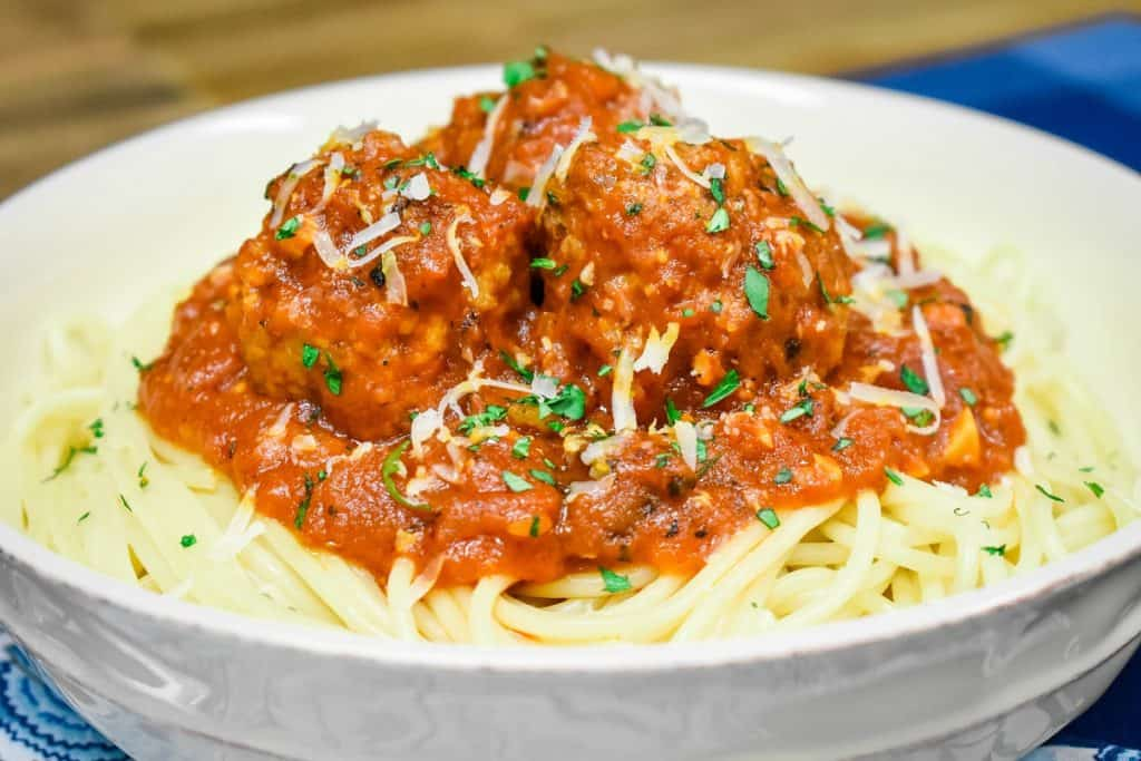 Italian sausage meatballs in a red sauce, served on a bed of spaghetti in a white bowl and garnished with chopped parsley and grated Parmesan cheese.