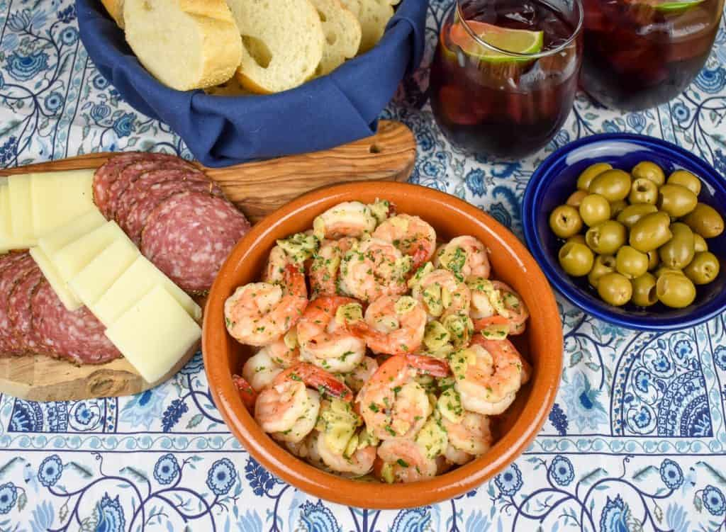 Camarones al ajillo served in an orange clay bowl with salami, cheese, olives, sliced bread and sangria served in the background.