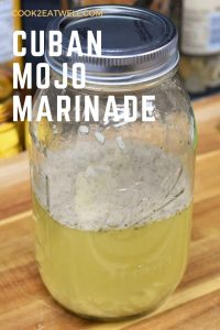 Mojo marinade in a large canning jar, displayed on a wood cutting board.
