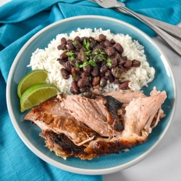 Pieces of the Cuban roast pork served with white rice and black beans on an aqua plate with an aqua linen and garnished with two lime wedges.