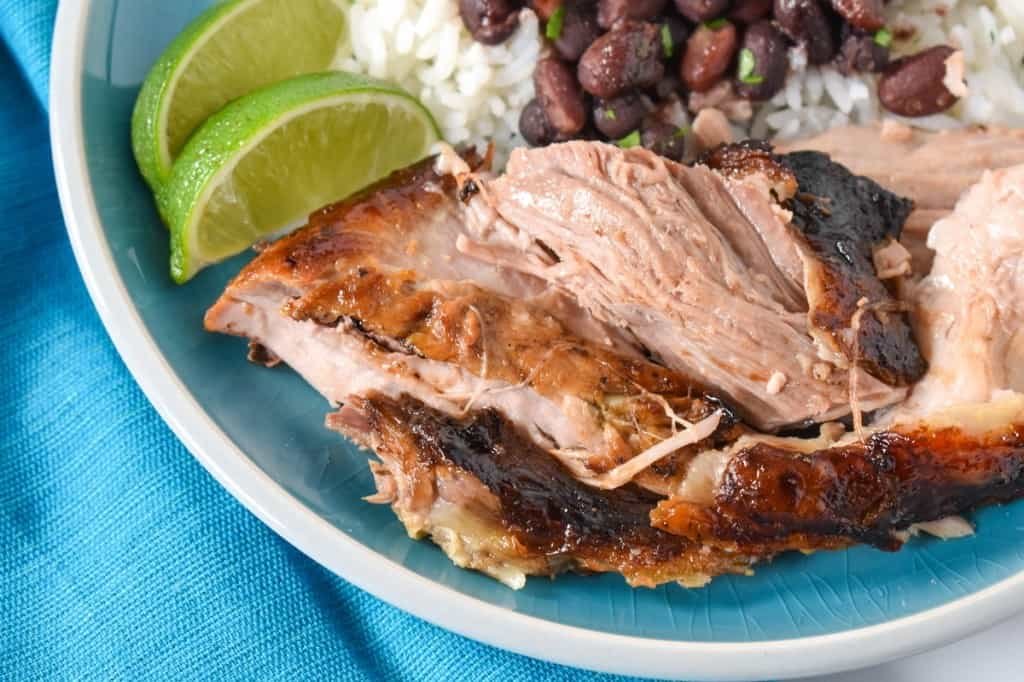 A close up image of pieces of roast pork on an aqua plate and linen, served with white rice and black beans and two lime wedges.