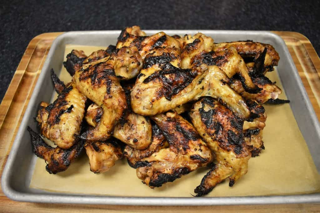 Grilled chicken wings with golden and caramelized skin piled on a sheet pan