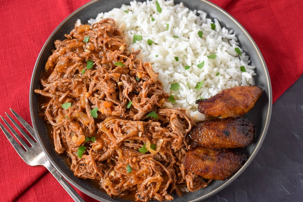 The finished ropa vieja served with white rice and fried sweet plantains on the side.