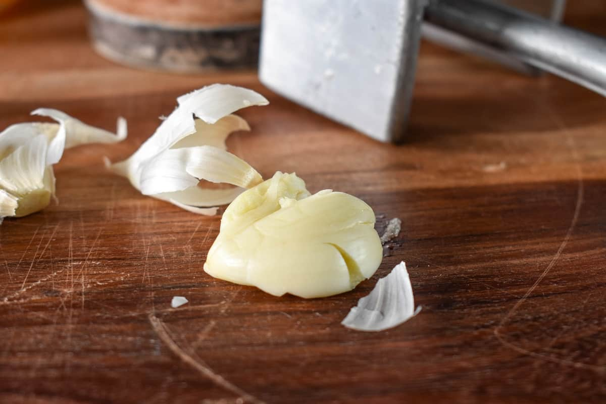 A smashed garlic clove on a wood cutting board.